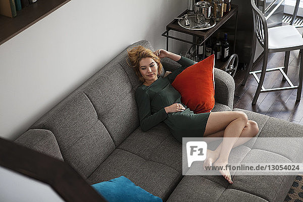 High angle view of woman relaxing on sofa at home