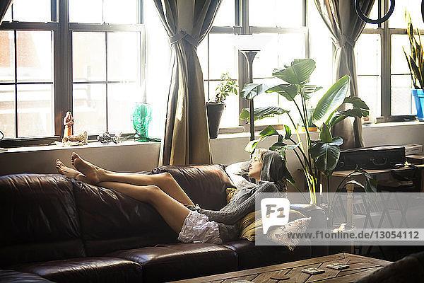 Seitenansicht einer Frau  die zu Hause auf dem Sofa liegt