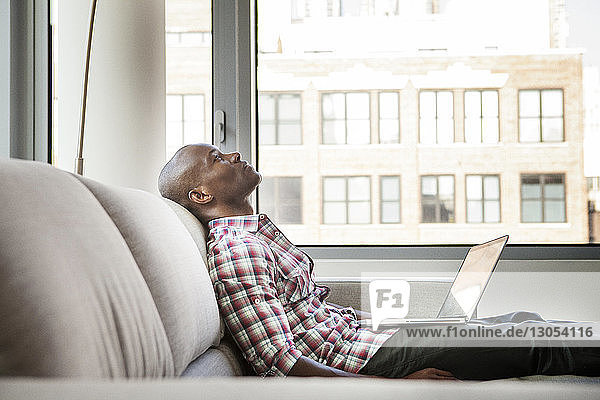 Tired man with laptop computer leaning on sofa at home