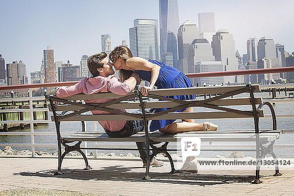 Frau lehnt auf Bank und küsst Mann gegen Geländer