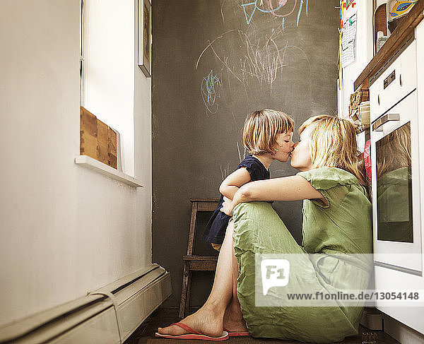 Daughter kissing mother at home