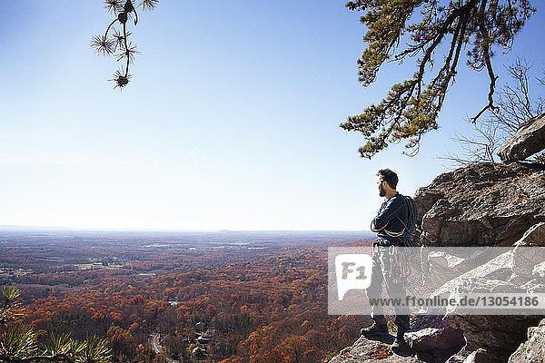 Mann steht auf Felsen gegen den Himmel