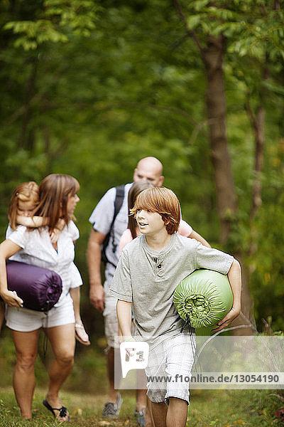 Glücklicher Junge trägt Schlafsack mit Familie im Wald spazieren