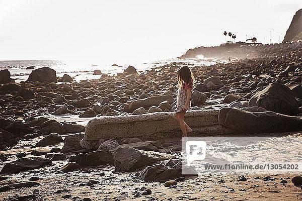 Seitenansicht eines Mädchens,  das bei Sonnenuntergang am Felsstrand steht