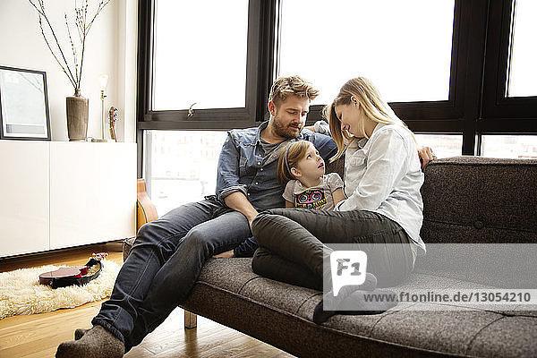 Familie sitzt auf der Couch im Wohnzimmer