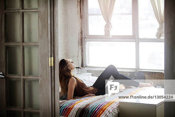Full length of woman relaxing on bed at home