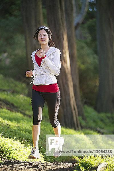 Junge Frau joggt auf dem Feld gegen Bäume