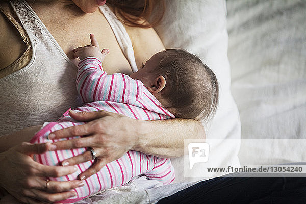 Cropped image of mother feeding baby girl at home