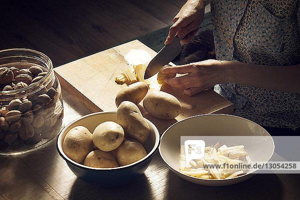 Hochwinkelaufnahme einer Frau  die zu Hause Kartoffeln auf einem Schneidebrett schneidet