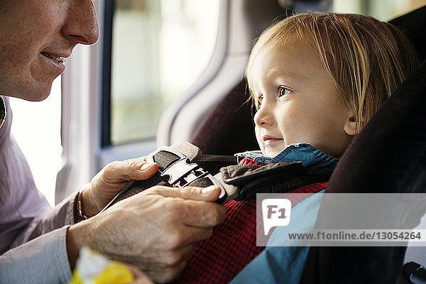 Beschnittenes Bild des Vaters  der den Sicherheitsgurt des Sohnes im Auto anlegt