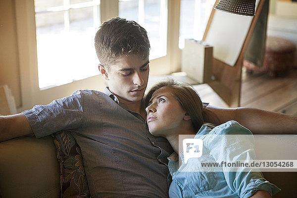 Frau lehnt sich an Mann an und entspannt sich auf Sofa