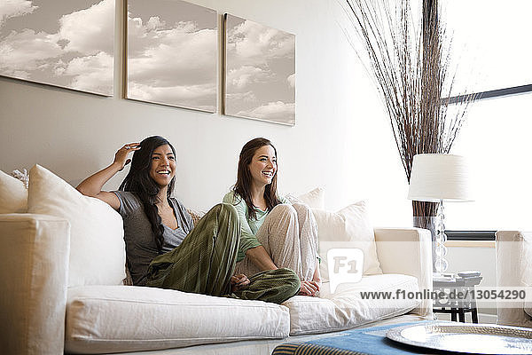 Happy female friends sitting on sofa at home