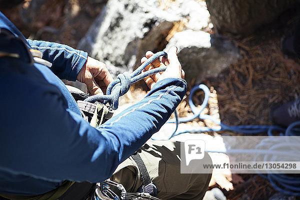 Hochwinkelansicht eines Mannes  der sich auf das Klettern am Fels vorbereitet