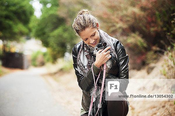 Glückliche Frau umarmt Hund auf der Straße