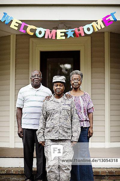 Porträt einer Soldatin  die mit ihren Eltern vor dem Haus steht