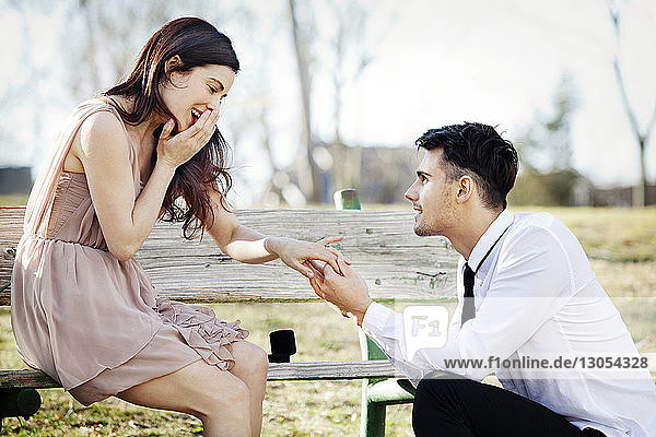Glückliche Frau sitzt auf Bank  während ein Mann im Park einen Heiratsantrag macht