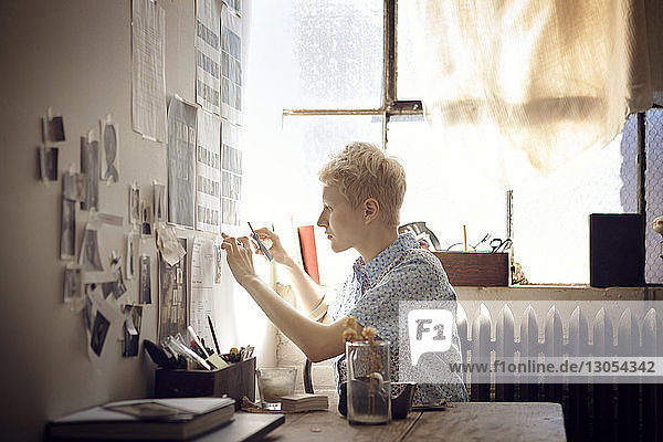 Woman sticking photographs on wall at home