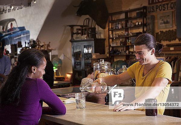 Männlicher Besitzer schenkt Getränk für Kunden im Café ein