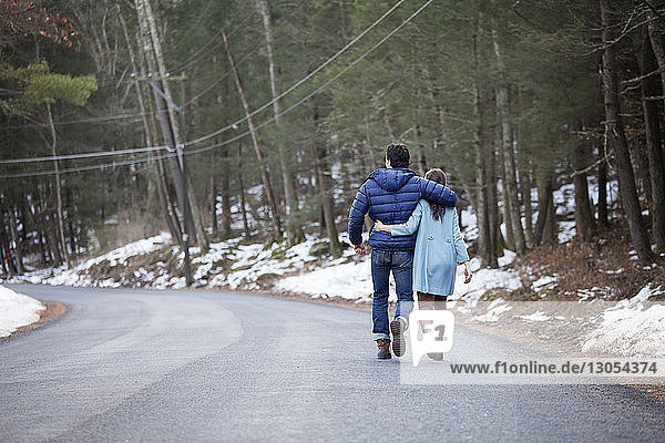 Rear view of couple walking on road