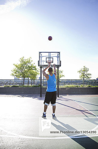 Rear view of man throwing basketball in hoop against sky during sunny day