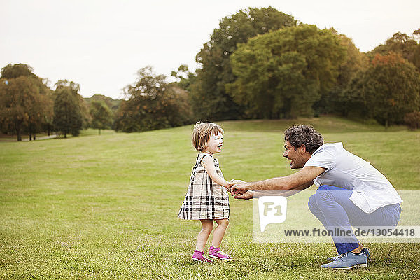 Seitenansicht des Vaters kauernd  während er die Hände der Tochter im Park hält
