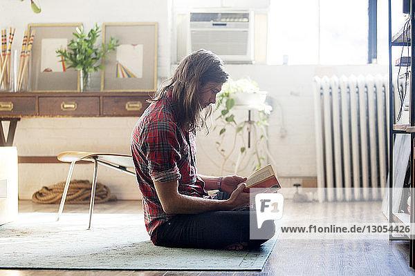 Seitenansicht eines zu Hause sitzenden Mannes beim Lesen eines Buches