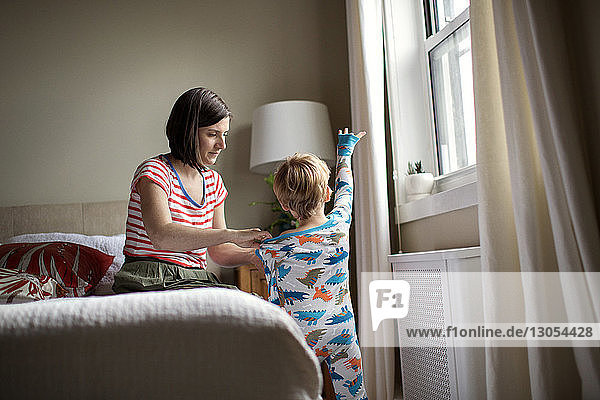 Mother dressing son while sitting on bed in room