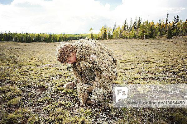 Mann in Tarnkleidung gräbt auf dem Feld