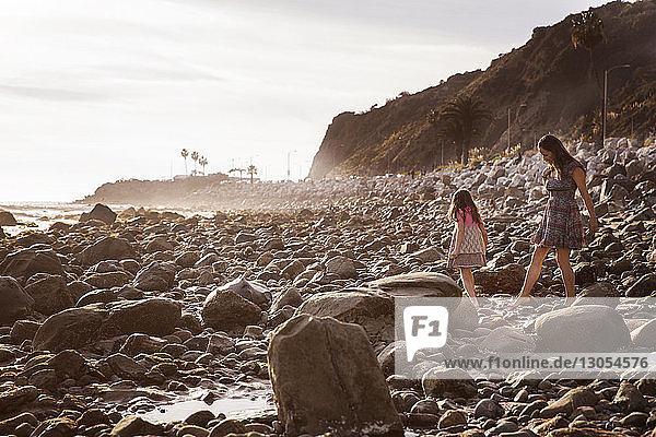 Mutter und Tochter gehen bei Sonnenuntergang am Felsstrand spazieren