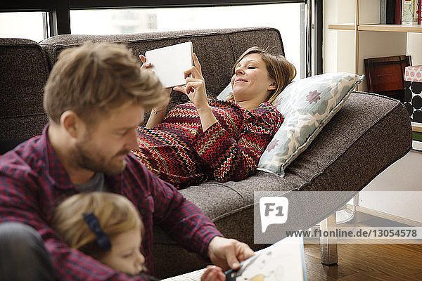 Vater und Tochter lesen ein Buch von einer Frau am Tablet-Computer  während sie sich auf der Couch entspannen