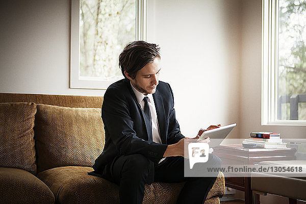 Businessman using tablet computer while sitting on sofa at home