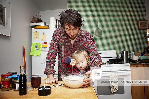Vater hilft Sohn beim Kochen zu Hause