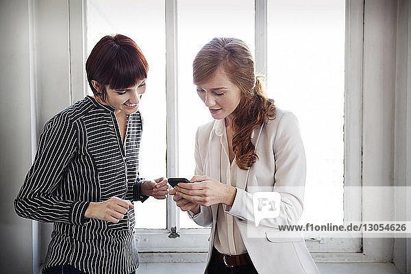 Businesswomen using phone in creative office