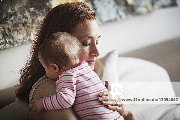 Mutter umarmt Tochter  während sie zu Hause sitzt