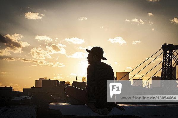 Scherenschnitt eines Mannes  der auf der Stützmauer einer Terrasse sitzt