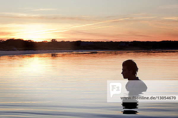 Man swimming in lake against sky during sunset