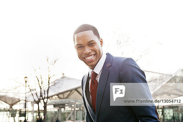Portrait of young businessman against clear sky