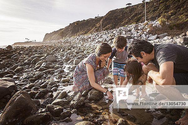 Familie taucht Finger bei Sonnenuntergang am Strand ins Wasser