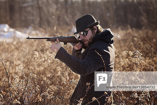 Mann zielt mit Gewehr  während er bei Pflanzen steht