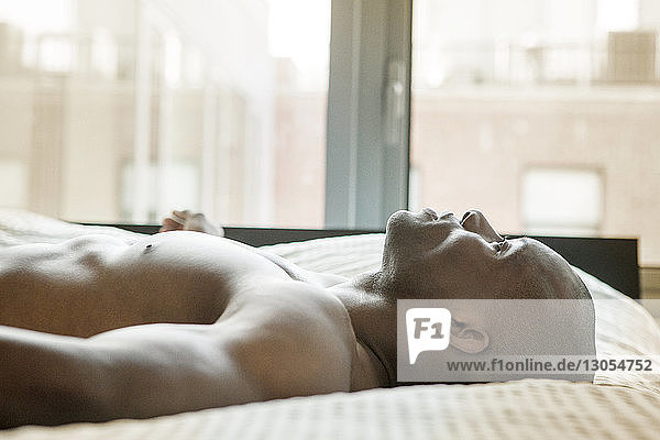 Side view of shirtless man relaxing on bed at home