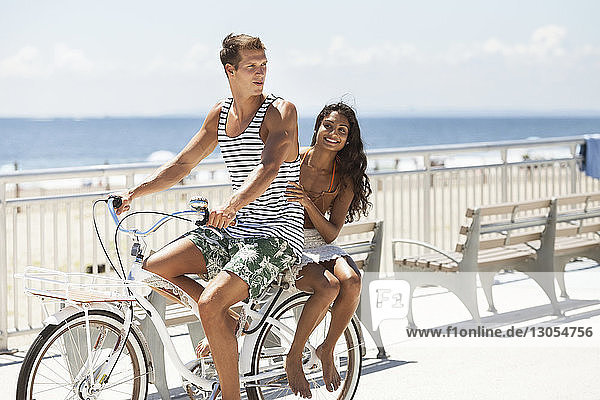Happy couple cycling on pier against sky