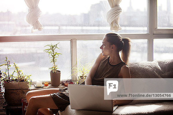 Woman looking away while sitting with laptop computer at home