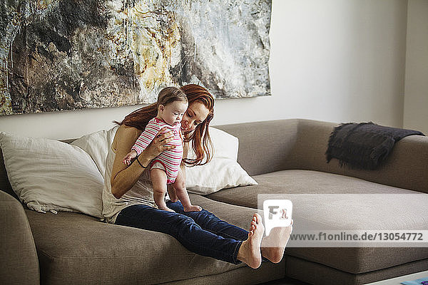 Mother teaching baby girl to walk while sitting on sofa at home