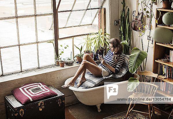 Hochwinkelansicht einer Frau  die auf einer Badewannencouch im Wohnzimmer sitzt
