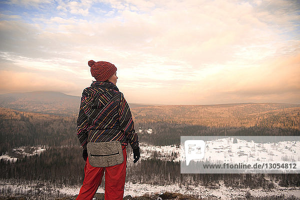Woman standing on mountain during winter against cloudy sky