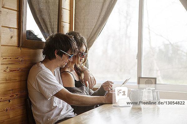 Paar benutzt Tablet-Computer im Café