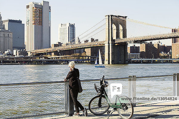 Woman looking at Brooklyn Bridge over East River while standing on promenade