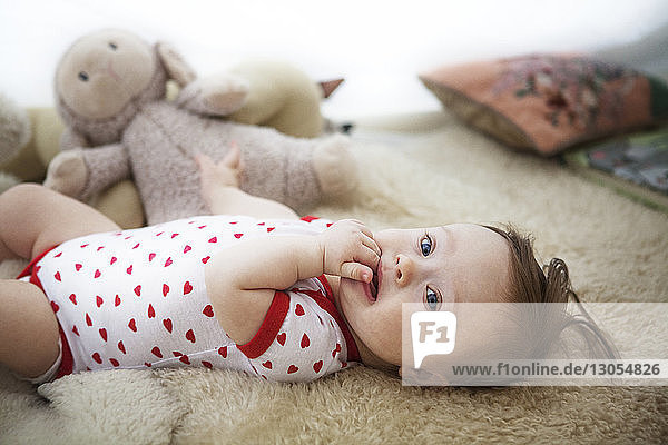 Portrait of baby girl lying at home