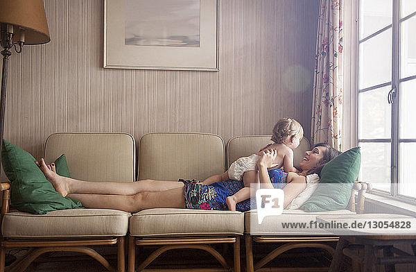 Glückliche Mutter spielt mit ihrem Sohn  während sie zu Hause auf dem Sofa liegt