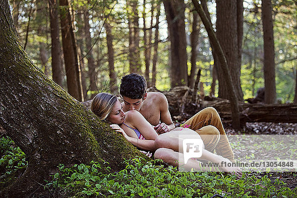Affectionate couple romancing by tree in forest